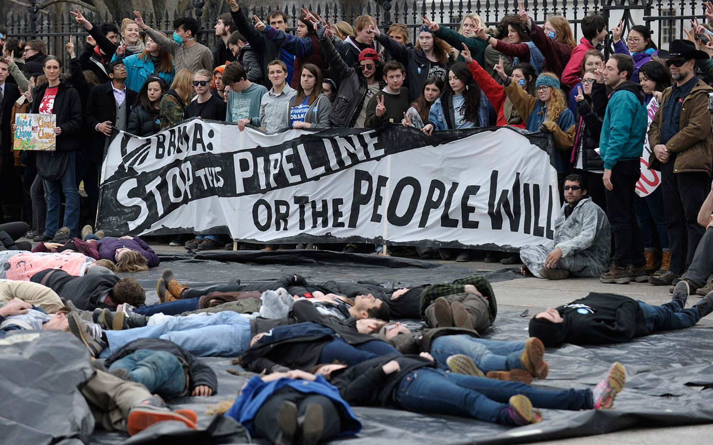 Several hundred students and youth who marched from Georgetown University to the White House to protest the Keystone XL Pipeline wait to be arrested outside the White House in Washington, Sunday, March 2, 2014. (AP Photo/Susan Walsh)