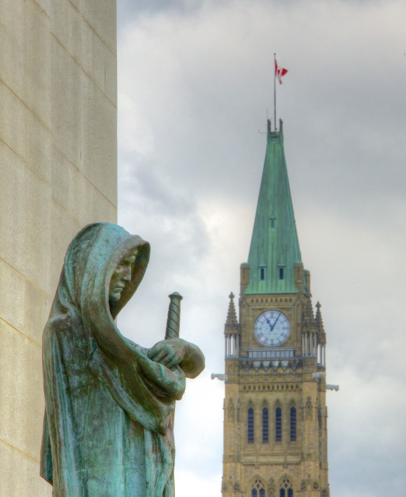 The statue Ivstitia (Justice) looks outward from the Supreme Court of Canada, with the Peace Tower in the near distance.
