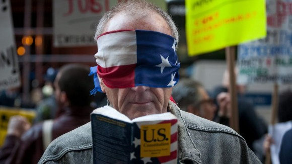 A protester wears a blindfold and holds a copy of the U.S. Constitution during a protest outside the New York State Republican Gala in New York, U.S., on Thursday, April 14, 2016. Michael Nagle / Bloomberg