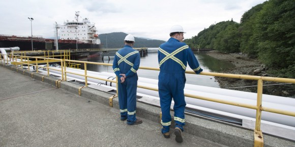 Kinder Morgan employees stand on the dock at the Trans Mountain Expansion Project in Burnaby, British Columbia, Thursday, June 4, 2015. THE CANADIAN PRESS/Jonathan Hayward