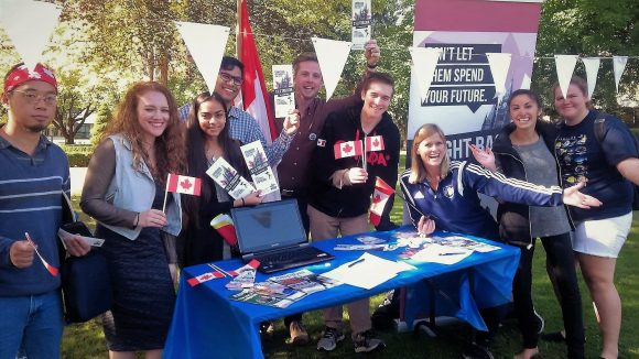 Generation Screwed Coordinator Michael Loughrun and students gather at a Trinity Western University club fair to raise awareness in September 2016 about the mounting debt in Canada.