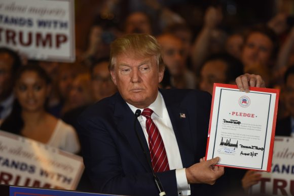 New York City - NY - USA - September 3 2015: Republican presidential candidate Donald Trump hold up signed agreement during press conference at Trump Tower to announce he has signed a pledge not to run as an independent candidate