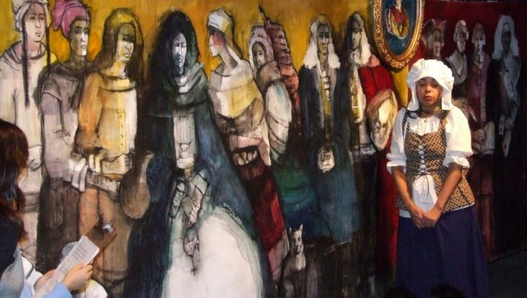 Black women is pictured against mural, begging questions of political correctness in the history of slavery in Quebec.