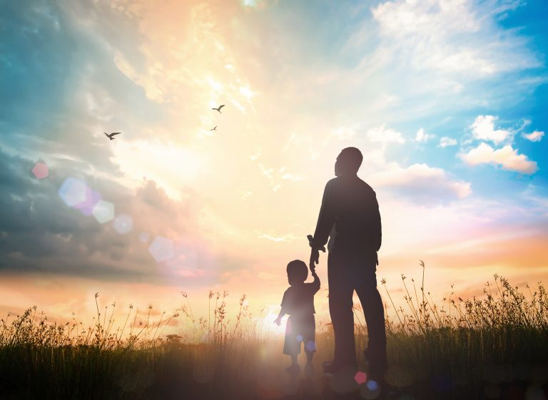 A father and son stand hand-in-hand in a field looking up at the sky. Invoking a strong sense of bond felt when one doesn't experience fatherlessness