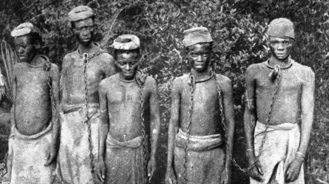 Five young enslaved black men in chains are shown. Victims of the slavery industry in Zanzibar.