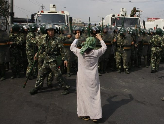 Pictured is an Uyghur woman in China being confronted by armed policemen. Speaking out against the human rights violations of the Uyghur minority is a way Canada could stand up in the Canada-China relationship