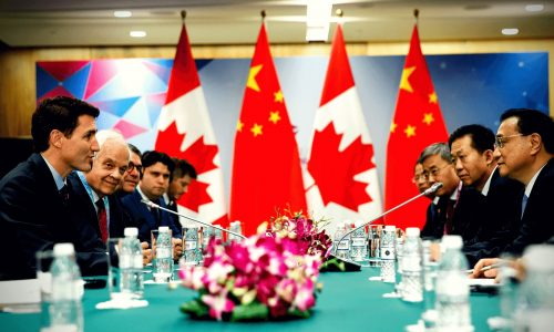 Picture of Canadian and Chinese officials engaged in official diplomatic talks, a key role in Canada-China relations.