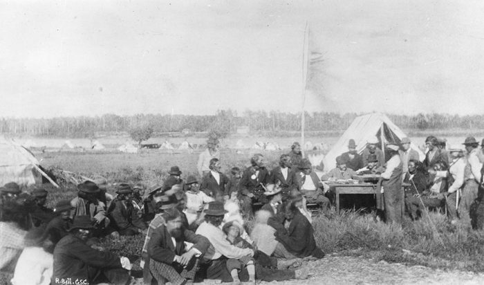Natives in Manitoba are pictured receiving their treaty money, reflecting Sir John A. Macdonald's commitment to treaty making over conflict.