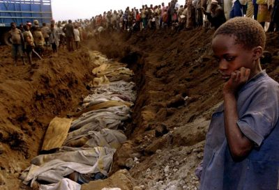 A Rwandan genocide survivor looks upon a mass grave outside Kigali in 1994.
