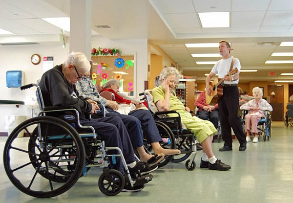Guitarist entertaining residents of Canadian long-term care facility.
