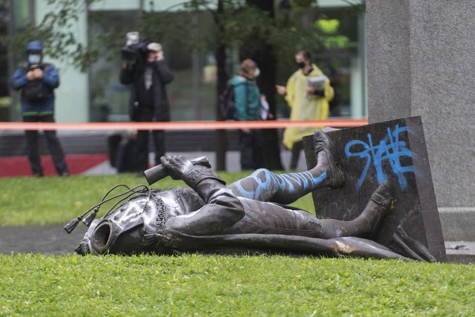 Picture is of a beheaded and fallen statue, an act against history that invites themes seen in the French Revolution.
