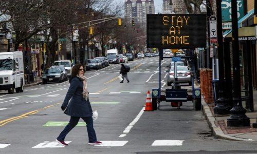 A sign in Inman Square in Cambridge informing residents to stay home during the Cornavirus epidemic. (Jesse Costa/WBUR)