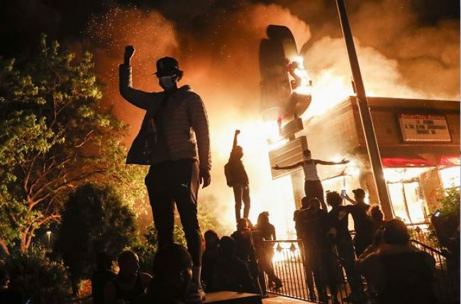 The picture is of destruction following a protest, drawing connections to the themes and violence seen in the French Revolution.